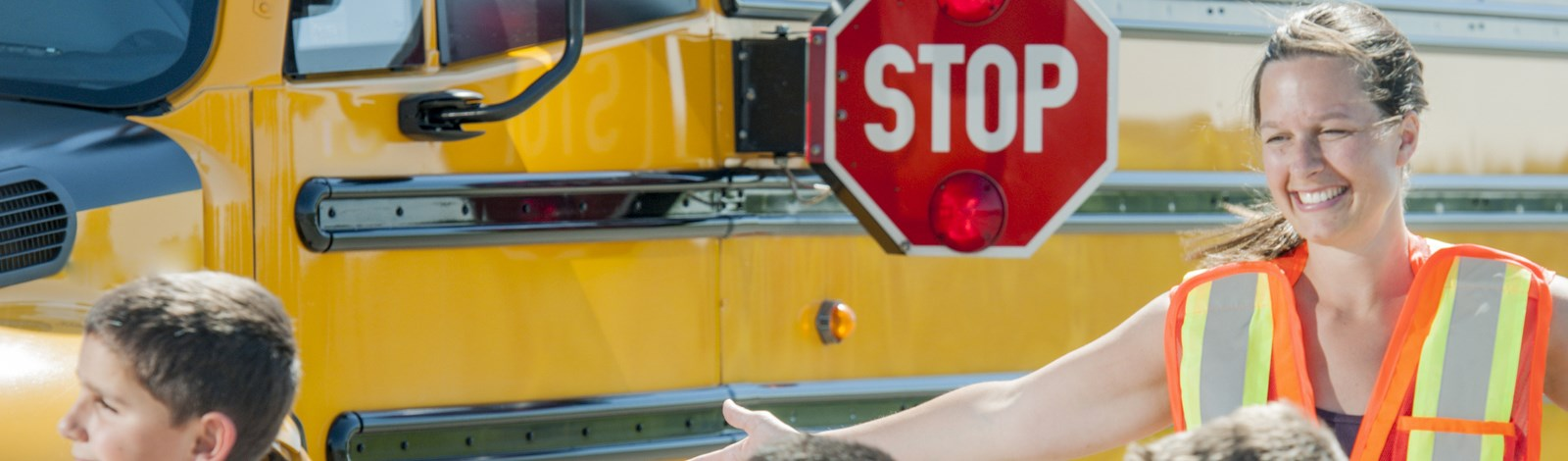 School bus with Stop sign arm out with the words Stop on the sign