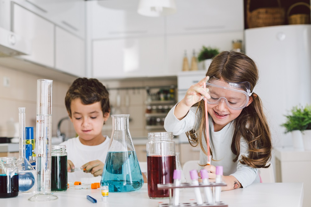 Siblings doing science experiment at home