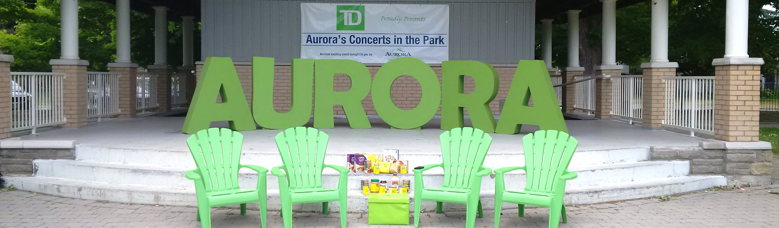 Concerts in the park stage with AURORA letters and green chairs
