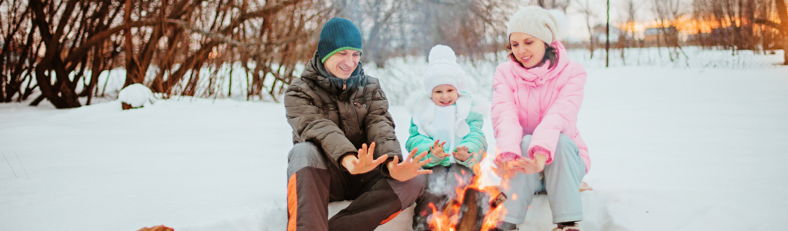 Dad, mom and child outdoors winter in front of campfire