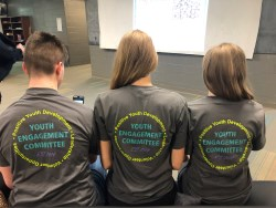 3 youth showing off the back of their youth engagement t shirts